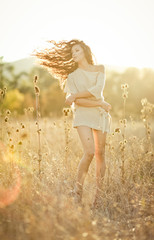 Young woman with beautiful curly hair posing in field at sunset