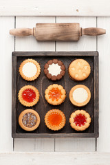 Cookies with chocolate and jam in  wooden box and a rolling pin