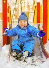 Happy kid on children playground in winter