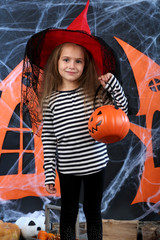Little girl in hat with pail for candy