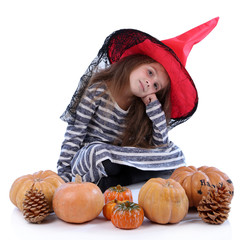 Little girl Witch in hat with pumpkins isolated on white