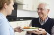 Leinwanddruck Bild - Carer Serving Lunch To Senior Man