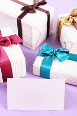 Cute presents with greeting card on light blue uneven