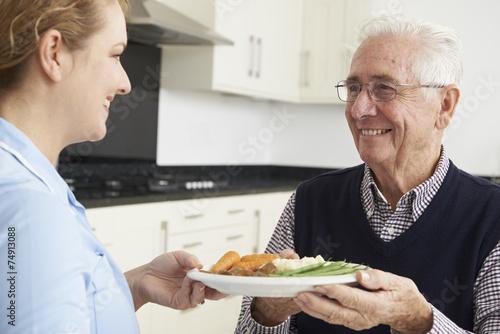 Leinwanddruck Bild Carer Serving Lunch To Senior Man