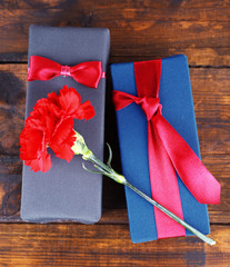 Two gift boxes with red carnation on wooden background