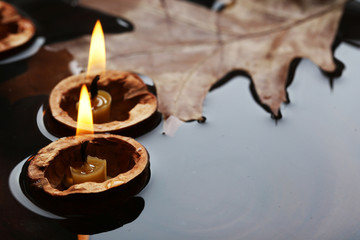 Leaf and nutshells with candles floating in water