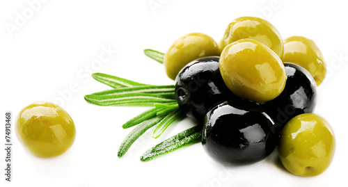 Leinwandbild Motiv Green and black olives with long leaves isolated on white