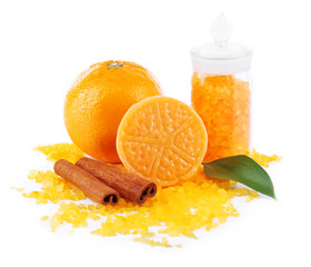 Bottle of bath salt with fresh orange, bar of soap and cinnamon