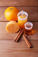 Bottles of essential oil and bath salt with orange, bar of soap