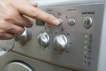 Woman Selecting Economy Program On Washing Machine To Save Energ