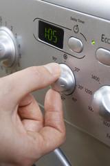 Woman Selecting Cooler Temperature On Washing Machine To Save En