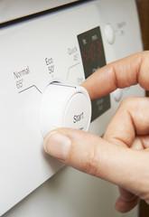 Close Up Of Woman Selecting Economy Program On Dishwasher