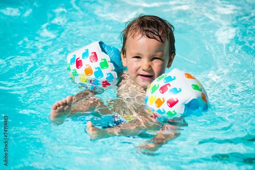 petit garçon avec brassards dans l'eau - 74914463