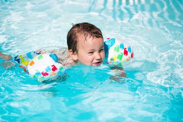 enfant avec brassards dans une piscine