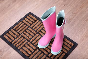 Pink wellington boots on door mat in room