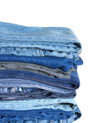 Stack on many jeans isolated on white close-up