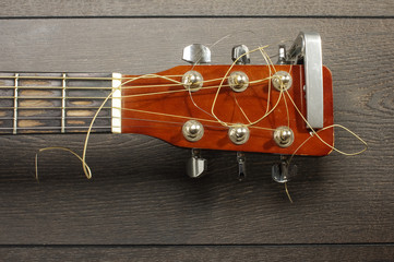 Top view of guitar headstock on the wooden table