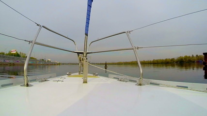 Sailboat passing buoy on wide city river, sailing, yachting, POV