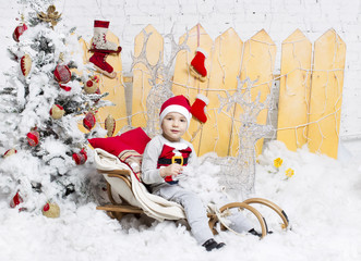 Little boy in Christmas costume sitting on a Christmas tree