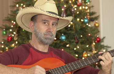 A Cowboy with a Guitar by a Christmas Tree