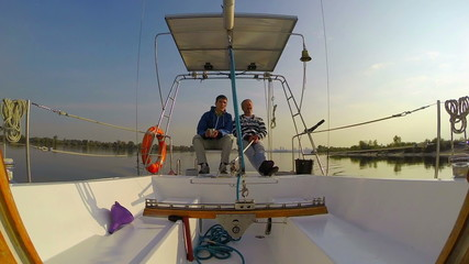 Two yachtsmen sitting and talking. Yachting, outdoor activities