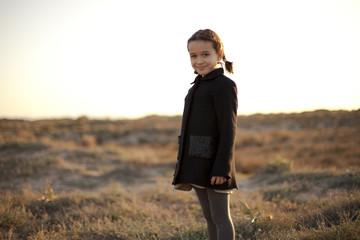Plano americano de niña en dunas al atardecer