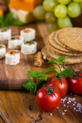 tomatoes with cheese snacks on wooden board