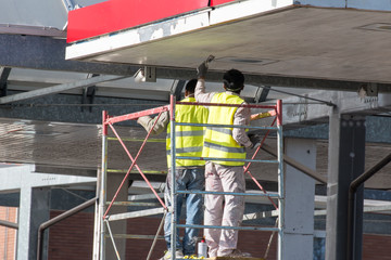 worker on a scaffold under roofing