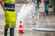 road spurt water beside traffic cones and a technician - 74919259