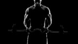 Fototapety Close up of young muscular man lifting weights over dark backgro