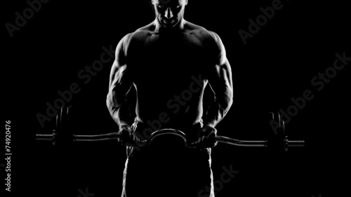Close up of young muscular man lifting weights over dark backgro - 74920476