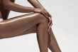 Beautiful woman tan legs. Against white wall. - 74921077