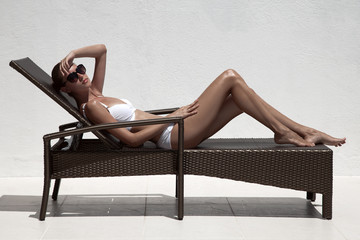 Beautiful tan female model sunbathing in bikini on chaise-longue