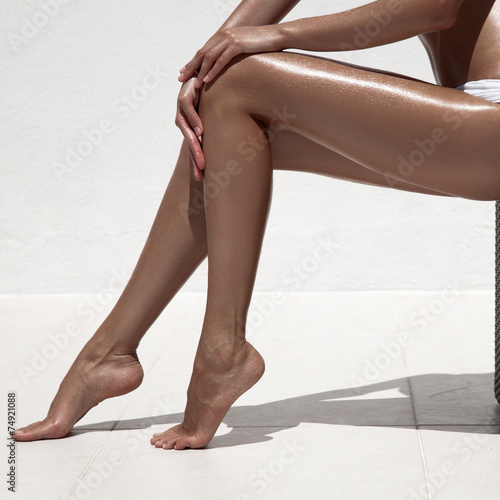 Beautiful woman tan legs. Against white wall. - 74921088