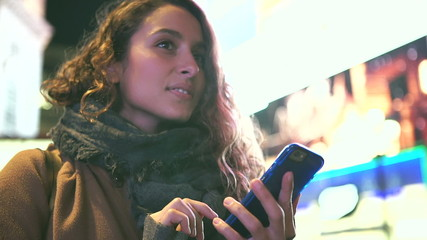 Attractive young woman using her phone in the city at night