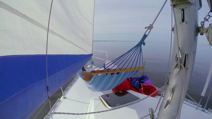 Person relaxing in hammock on sailing yacht, holiday, vacation