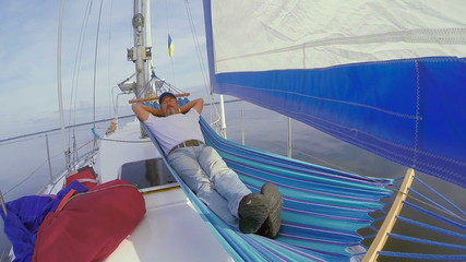 Senior man sleeping in hammock on sailing yacht, vacation, rest