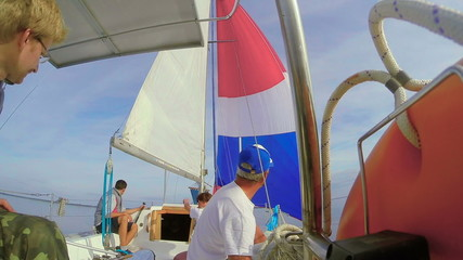 Four people crew on sailing yacht, open sea, traveling, vacation