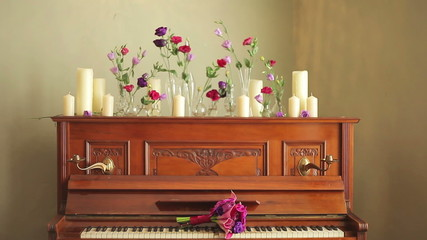old beautiful piano with bouquets of flowers and candles