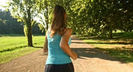 Active Young Female Running Through Park Sun Flare Fitness