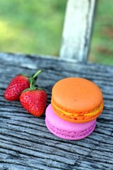 Macaroons on a wood table with a strawberry