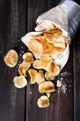 Potato chips over dark wooden background
