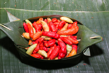Organic Red Spicy Fresno Peppers on banana leaf