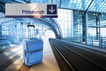 Departure for Pittsburgh. Blue suitcase at the railway station