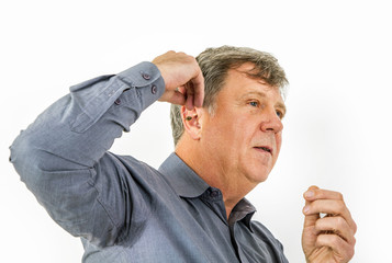 serious man in shirt handling his  hearing aid