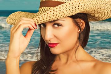 Портрет красивой молодой женщины в шляпе на фоне моря.
