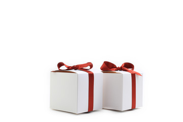 Little white colored present boxes with red ribbons