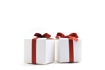 Closeup of two little gift boxes with red ribbons