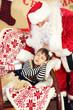Santa Claus giving  present to sleeping little cute girl