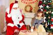Little cute girl giving glass of milk to Santa Claus near